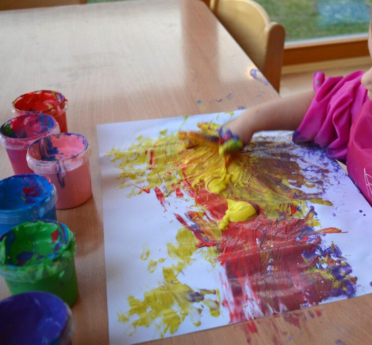 Kleindkind malt mit Fingern