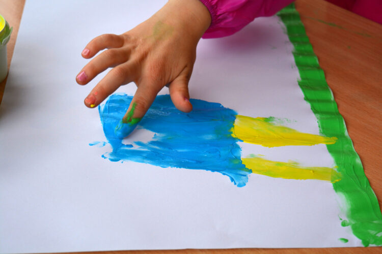Kinderhand malt mit Fingerfarbe