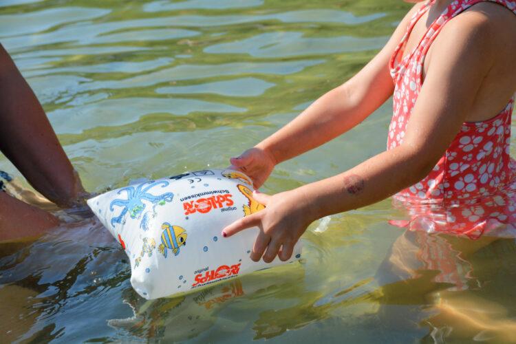 Schlori Schwimmkissen in Kinderhänden