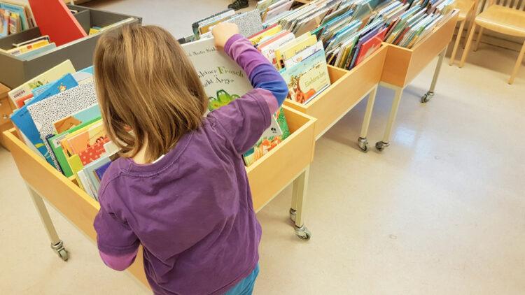 Kinderbücher stöbern in der Bibliothek