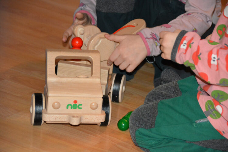 Kinder spielen mit Nic Holzspielzeug