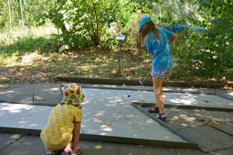 Kinder spielen Minigolf