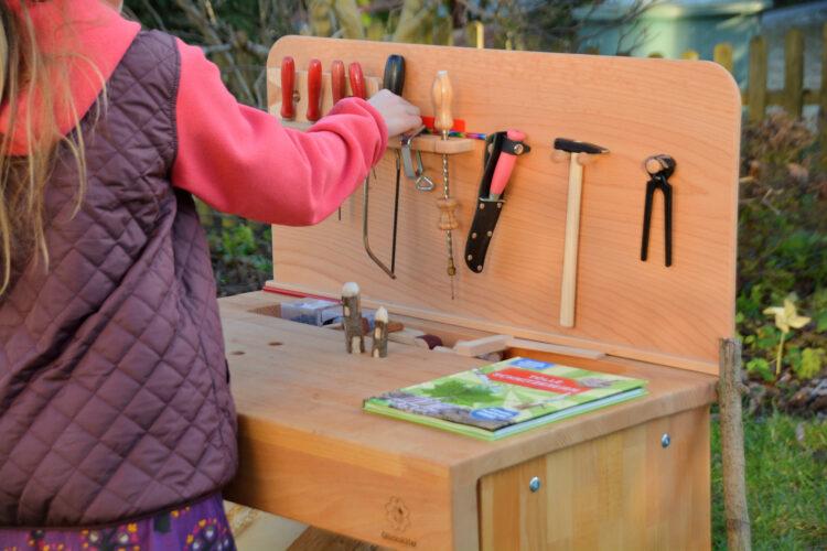 Kind räumt Holz-Werkbank auf